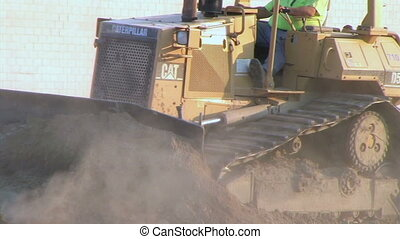 Dozer Clears Edge of Road - Bulldozer pushing dirt.