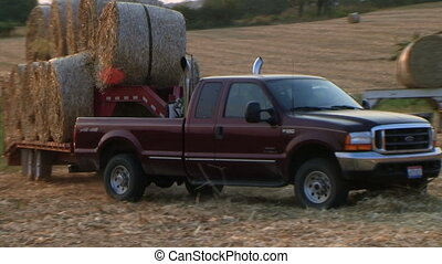 Trucks Hauling Hay Bales - Close-up of trucks hauling round...