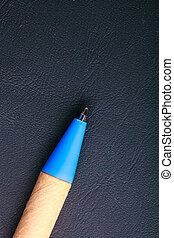 Blue pen writing material on black leather background - Blue...
