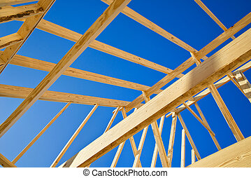 New construction home framing against blue sky, closeup of...