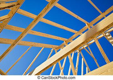 New construction home framing against blue sky, closeup of...