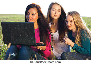 three young beautiful woman with a laptop sitting in the field on sky background
