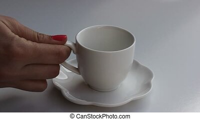 Tea time - Woman's hand putting down a tea cup and pouring...