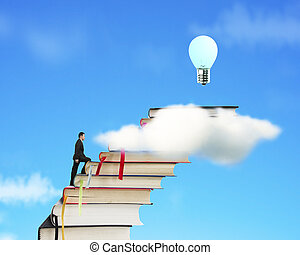 Businessman climbing on stack of books to reach bulb -...