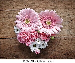 pink and white flowers heart on a wood background