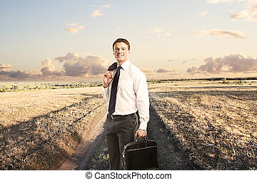 happy man on country road - man with briefcase standing on a...