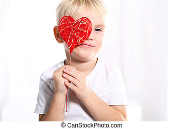 boy shows a red Valentine heart - Little caucasian boy shows...