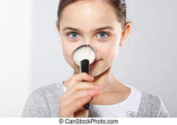 Pretty girl powdering her nose - Young teenage girl with...