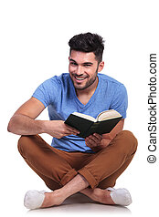 seated young casual man reading a book and smiles