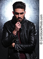 pensive fashion young man in leather jacket