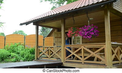 woman log house gate - Woman walk through small wooden gates...