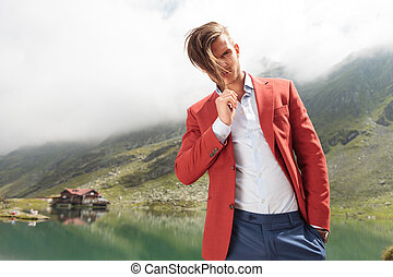 man pulling his hair in front of a mountain lake - fashion...