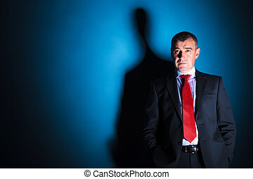 old business man with hands in pockets looking away on blue...