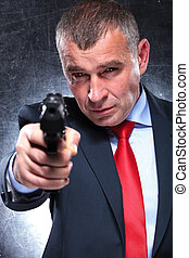 old killer in suit and tie pointing his gun - serious old...