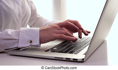 Business woman typing on a laptop. - Dolly shot of a...