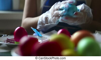 Coloring easter eggs - Woman coloring easter eggs. Rack...