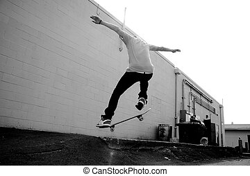 Skateboarder - A young skateboarder doing a stunt in an...