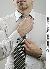 Tie knot - anonymous guy doing a tie knot in closeup frame