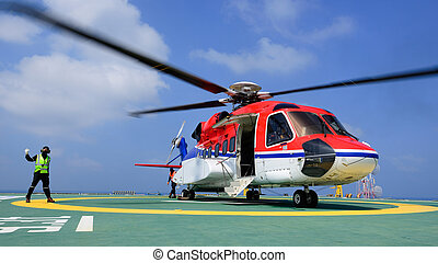 The helicopter landing officer give signal to passenger to...
