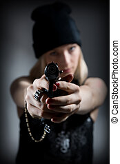 Portrait of a young girl with a gun. Hooligan in a dark cap...