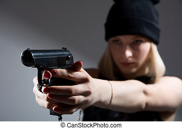 Portrait of a young girl with a gun in his hand. Hooligan in...