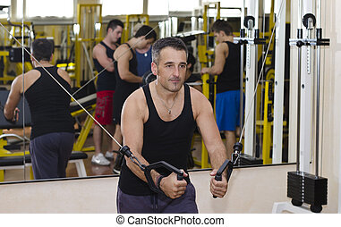 Middle aged man working out with gym equipment, exercising...