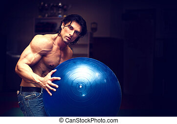 Muscular young man shirtless holding fitness ball