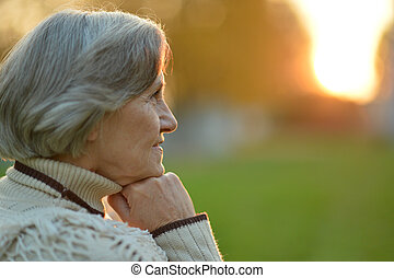 thinking senior woman in autumn park - Portrait of thinking...