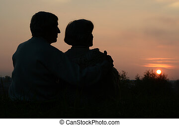 Elderly couple looking at sunset - Elderly couple sitting in...