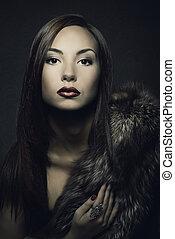 Woman beauty portrait in luxury fur coat. Dark background.