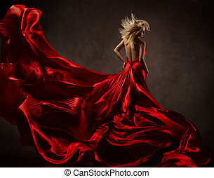 Woman in red waving dress with flying fabric. Back side view...