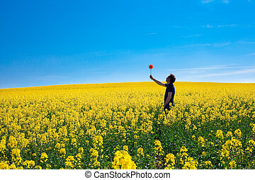 man with pinwheel standing in a field of yellow rape against the blue sky
