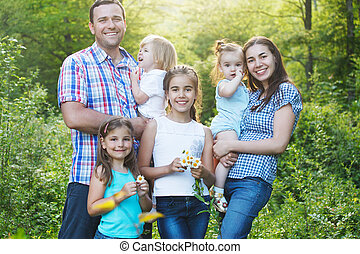 Happy young family with four children outdoors