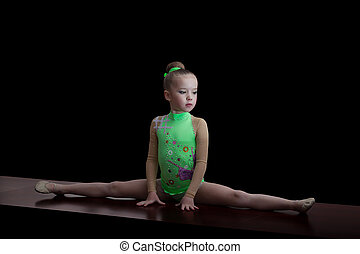 Little adorable gymnast in green leotard suit isolated on...