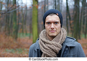 young man in the woods - young man with scarf and woolly hat...