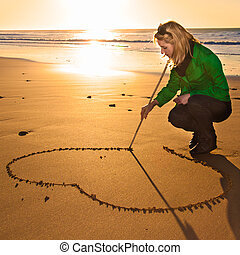 Woman drowing a heart shape in the sand. - Woman drowing a...