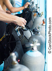 Guy checking the diving equipment.