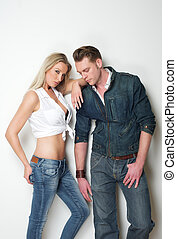 Young fashion couple posing against white background