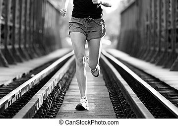 Active female athlete running on railaway tracks - Athlete...