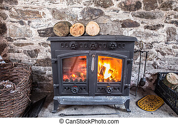 Cast iron wood stove burning logs against a robust stone...