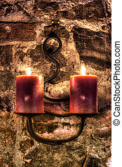 Two burning candles hanging from a robust wall