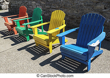 Colored Chairs - Row of colored adirondack chairs at high...