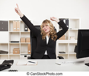 Jubilant businesswoman celebrating a success pointing and...