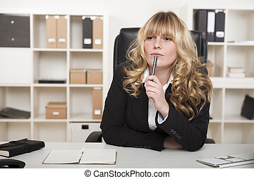 Young businesswoman sitting thinking at her desk as she...