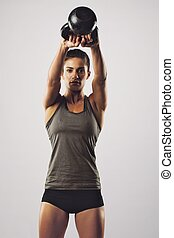 Woman working out with kettle bell - Young female doing...