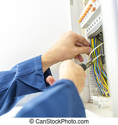 Electrician installing an electrical fuse box in a house...