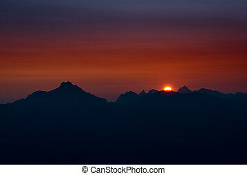 sunset at austrian alp mountains with red glowing sky