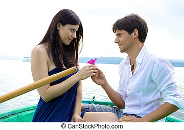 Boyfriend donating pink flower to girlfriend in love