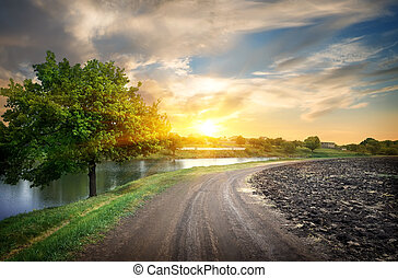 Country road and river - Sunset over the country road the...