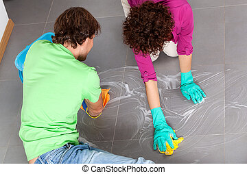 Couple during housework - Young couple cleaning kitchen...